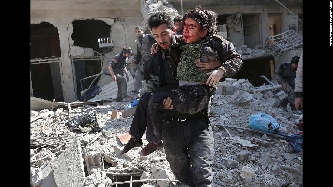A man rescues a child after a reported airstrike in the rebel-held town of Hamouria on Wednesday, February 21. Syria says it is targeting terrorists in Eastern Ghouta.