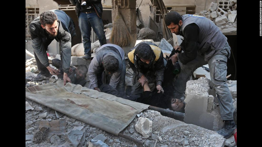 Members of a Syrian civil-defense team rescue a man in Hamouria on February 21.