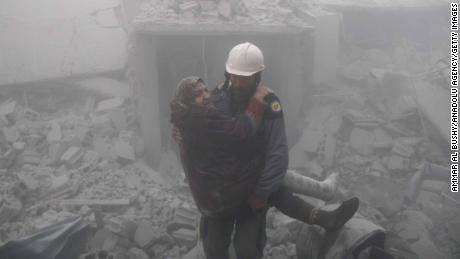 A rescue worker carries a woman from the wreckage of buildings hit by an airstrike over Erbin in Eastern Ghouta on Tuesday.