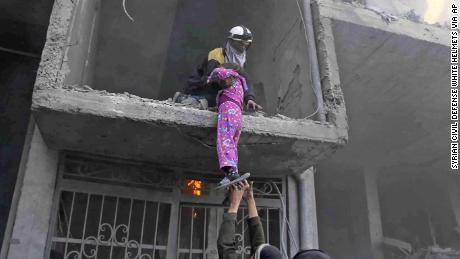 A photo provided Wednesday by the White Helmets volunteer group shows the rescue of a young girl from a building damaged by airstrikes and shelling in Eastern Ghouta.