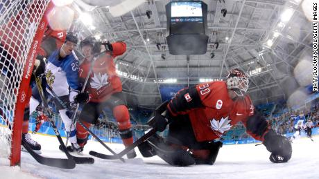 GANGNEUNG, SOUTH KOREA - FEBRUARY 21:  Jonas Enlund #25 of Finland and Cody Goloubef #27 of Canada compete for the puck as Ben Scrivens #30 makes a save in the first period during the Men's Play-offs Quarterfinals on day twelve of the PyeongChang 2018 Winter Olympic Games at Gangneung Hockey Centre on February 21, 2018 in Gangneung, South Korea.  (Photo by Matt Slocum - Pool/Getty Images)