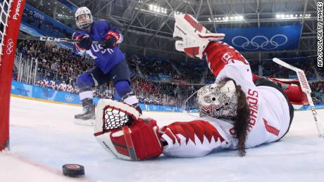 USA's Jocelyne Lamoureux-Davidson (L) scores on Canada's Shannon Szabados during the penalty-shot shootout in the women's gold medal ice hockey match.