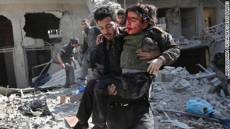 EDITORS NOTE: Graphic content / Syrians rescue a child following a reported regime air strike in the rebel-held town of Hamouria, in the besieged Eastern Ghouta region on the outskirts of the capital Damascus on February 21, 2018.  / AFP PHOTO / ABDULMONAM EASSA        (Photo credit should read ABDULMONAM EASSA/AFP/Getty Images)