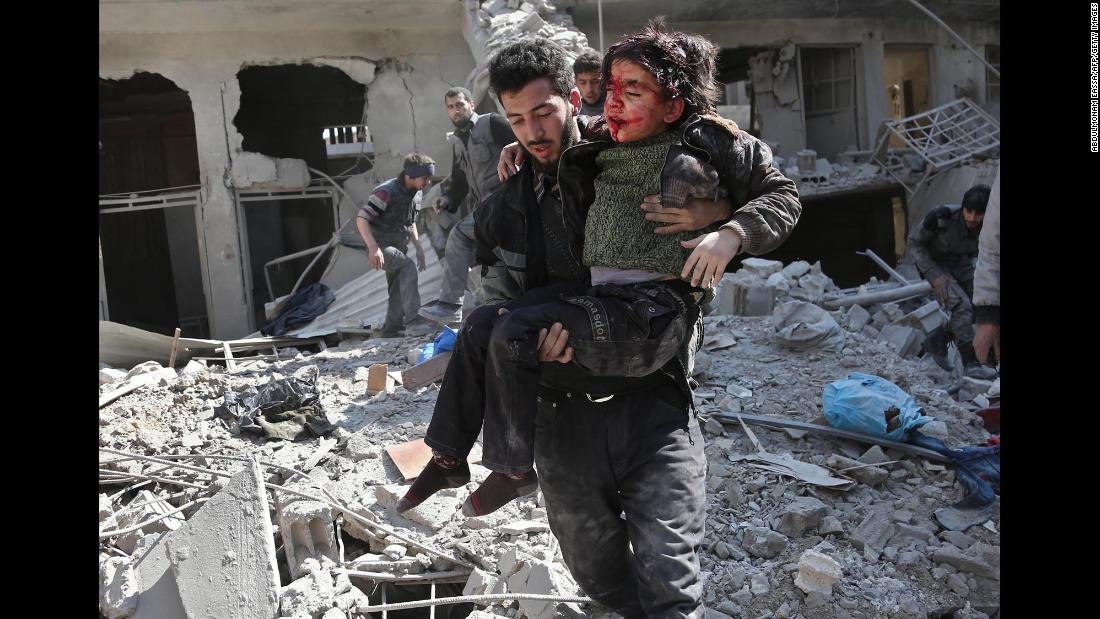 "A man rescues a child after a reported regime airstrike in the rebel-held town of Hamouria in Syria's <a href=""https://edition.cnn.com/2018/02/21/middleeast/syria-eastern-ghouta-bombardment-intl/index.html"" target=""_blank"">besieged Eastern Ghouta</a> region on Wednesday, February 21. As many as 300 people died over three days in the bombardment of the rebel enclave, medics and activists say."