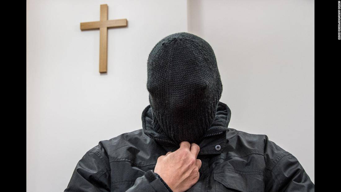 A former priest charged with sexually abusing five boys hides his face in his hat as he waits for his trial at court in Germany on Thursday, February 22.