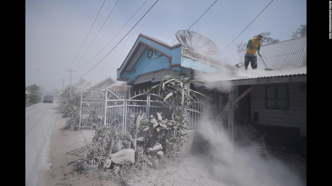 A man cleans debris from the roof of a house on Tuesday, February 20 after Mount Sinabung spewed volcanic ash into the air the day before in Indonesia.