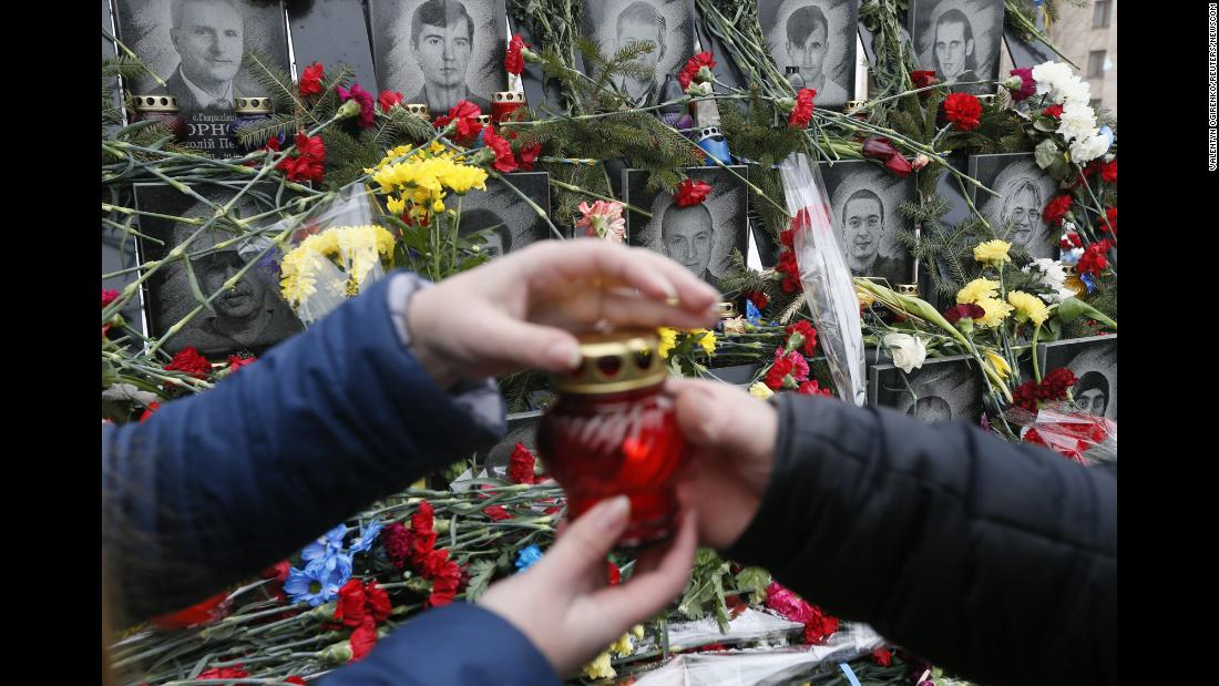 A candle is passed on Tuesday, February 20, during a commemoration ceremony at the monument to the people killed during the Ukrainian pro-European Union mass protests in 2014, in central Kiev, Ukraine.