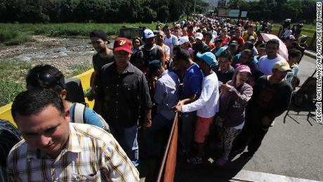 People queue to cross the Simon Bolivar international bridge from San Antonio del Tachira, in Venezuela, to Norte de Santander province in Colombia, on December 20, 2016 after Venezuela reopened the border crossing that it had closed as part of a messy crackdown on what it called currency hoarders. A pedestrian crossing over the Simon Bolivar Bridge -- joining the cities of San Antonio in Venezuela and Cucuta, Colombia -- reopened after a telephone conversation between the countries' presidents Monday night, according to Venezuelan information minister Ernesto Villegas. The crossing had been closed since December 12 as part of a currency reform that involved removing the 100-bolivar note from circulation.  / AFP / GEORGE CASTELLANOS        (Photo credit should read GEORGE CASTELLANOS/AFP/Getty Images)
