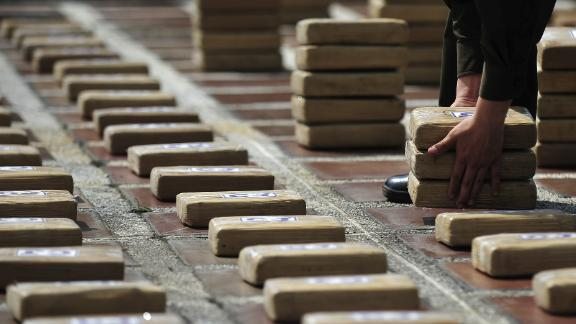 A Colombian police officer lays out packages of cocaine seized in the city of Cali