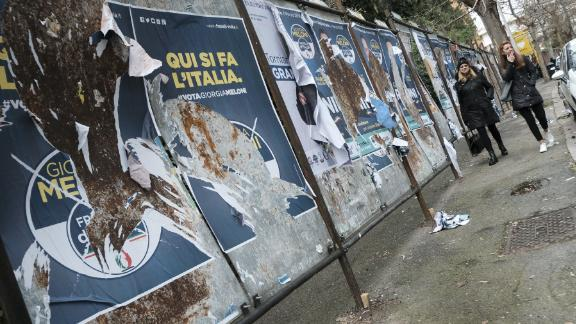 Women walk past  candidates' posters in Rome ahead of Sunday's general elections.