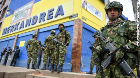 Colombian police and soldiers guard a Colombian supermarket after it was looted by vandals in the south of Bogota on February 22, 2018. An investigation by the Colombian public prosecutor's office of warehouses and a supermarket belonging to alleged frontmen of the demobilized FARC guerrilla triggered looting.   / AFP PHOTO / Raul ARBOLEDA        (Photo credit should read RAUL ARBOLEDA/AFP/Getty Images)