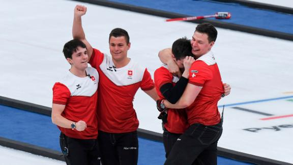 The Swiss men's curling team celebrates after winning the bronze-medal game against Canada.