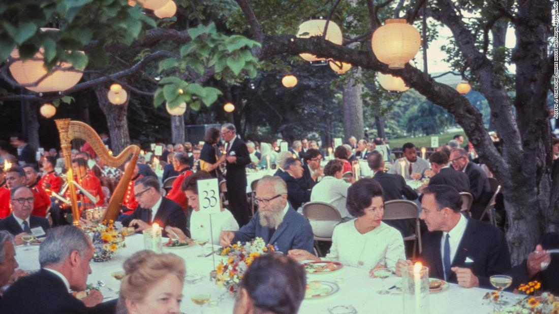 In this photograph first lady Lady Bird Johnson dines with actor Gene Kelly and photographer Edward Steichen at dinner during the White House Festival of the Arts.  On June 14, 1965 over 300 guests attended the White House Festival of the Arts to honor contemporary American artistic achievement. 65 works of art borrowed from 39 museums across the country were displayed in the East Wing and Jacqueline Kennedy Garden. The 14 hour event also featured a variety of performances in the East Room and the South Lawn including Duke Ellington, the Robert Joffrey Ballet, and the Louisville Orchestra.