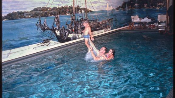 This photograph by Joseph J. Scherschel shows astronauts James McDivitt and Edward White and their families in the White House swimming pool. The McDivitt family is out of frame. They were invited to the White House following the successful Gemini 4 mission to space, which included 62 Earth orbits over four days and the first American spacewalk. The invitation followed their promotion by President Lyndon B. Johnson to the rank of lieutenant colonel the week before at an event at NASA's Manned Spaceflight Center in Houston, Texas, and the visit included an overnight stay at the White House. This pool was installed during the Franklin Roosevelt administration and was covered over during the Richard M. Nixon administration to create the Press Room.