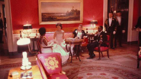 In this photograph President John F. Kennedy, first lady Jacqueline Kennedy, President Félix Houphouët-Boigny of the Ivory Coast, and first lady Marie-Thérèse Houphouët-Boigny of the Ivory Coast converse in the Red Room of the White House. The group was attending a State Dinner held in honor of President Houphouët-Boigny's State Visit on May 22, 1962.