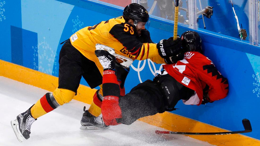 Germany's Felix Schutz checks Canada's Maxim Noreau into the boards during the first period of their semifinal game. Germany won 4-3.