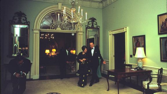 In this photograph President Lyndon B. Johnson walks Indian prime minister Indira Gandhi into the Center Hall prior to a State Dinner held in her honor on March 28, 1966. The Center Hall is located on the Second Floor of the White House, in the family quarters.