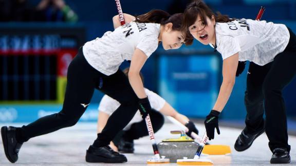 Japan's Yurika Yoshida, left, and Chinami Yoshida brush the ice during the match against South Korea.