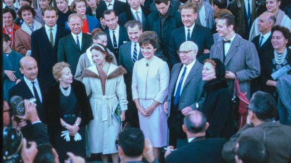 This photograph shows visitors on the North Portico after exiting the White House following a tour. First Lady Jacqueline Kennedy greets the group and poses for pictures.