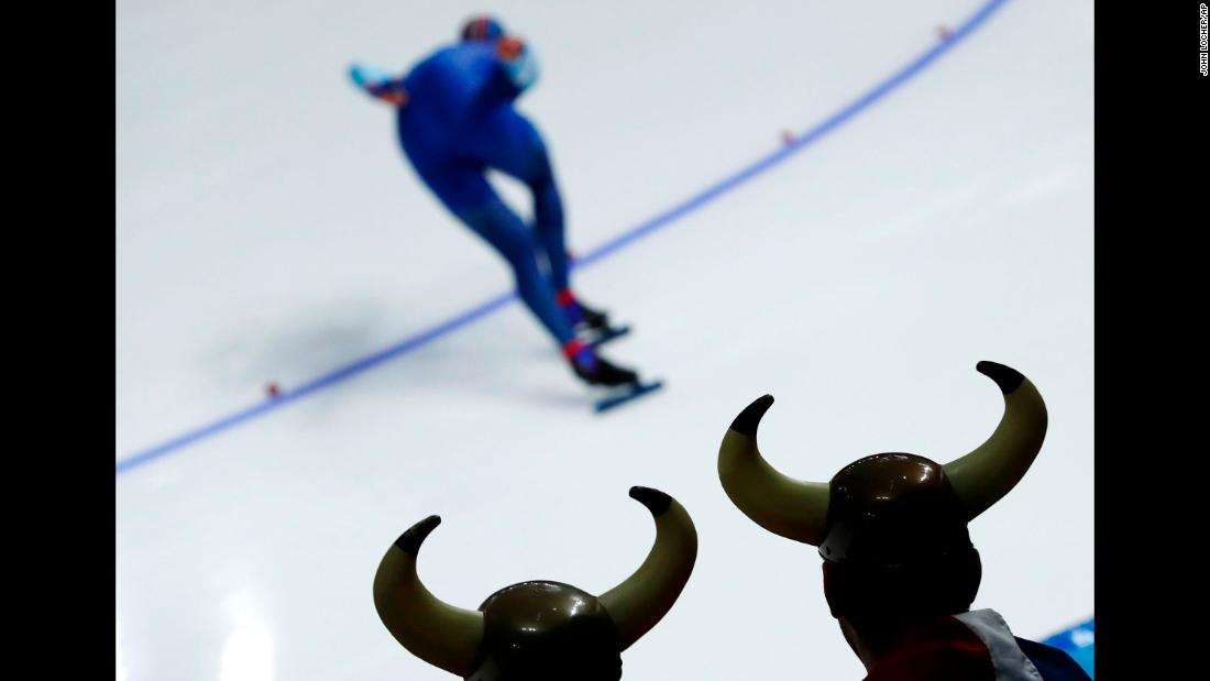 Two spectators dressed as vikings watch the 1,000-meter speedskating race.