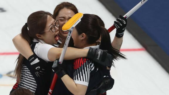 The South Korean women's curling team celebrate after defeating Japan to advance to the final.
