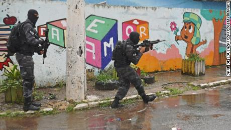 Special military police shock troops patrol near the Vila Kennedy favela in Rio de Janeiro, Brazil, on February 23, 2018. More than 3,000 soldiers supported Rio de Janeiro police Friday in a sweep of three violence-plagued favelas in the west of the Brazilian city, officials said. Brazilian President Michel Temer handed the military full control of security in Rio de Janeiro, in an increasingly desperate fight to tame runaway gang violence.  / AFP PHOTO / Carl DE SOUZA        (Photo credit should read CARL DE SOUZA/AFP/Getty Images)
