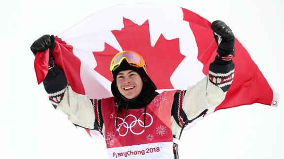 Sebastien Toutant celebrates with the Canadian flag after winning the big-air snowboarding event. The event was making its Olympic debut.