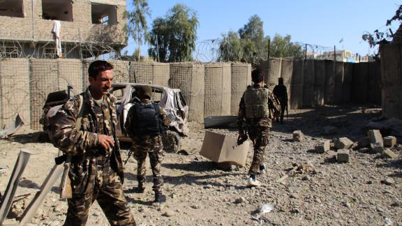Afghan security personnel examine the site of a car bomb attack in Lashkar Gah on Saturday.
