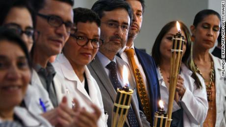 The former head of the OAS Mission to Support the Fight Against Corruption and Impunity in Honduras (MACCIH), Juan Jimenez Mayor (C), and Chilean Judge Daniel Urrutia (3rd-R) - both of whom resigned from the anti-corruption panel - hold torches during an event in which they are honored at the Honduran Medical Association, in Tegucigalpa on February 22, 2018.  Jimenez Mayor resigned from his post complaining of a lack of support from Organization of American States (OAS) Secretary-General Luis Almagro in the fight against corruption.  / AFP PHOTO / ORLANDO SIERRA        (Photo credit should read ORLANDO SIERRA/AFP/Getty Images)