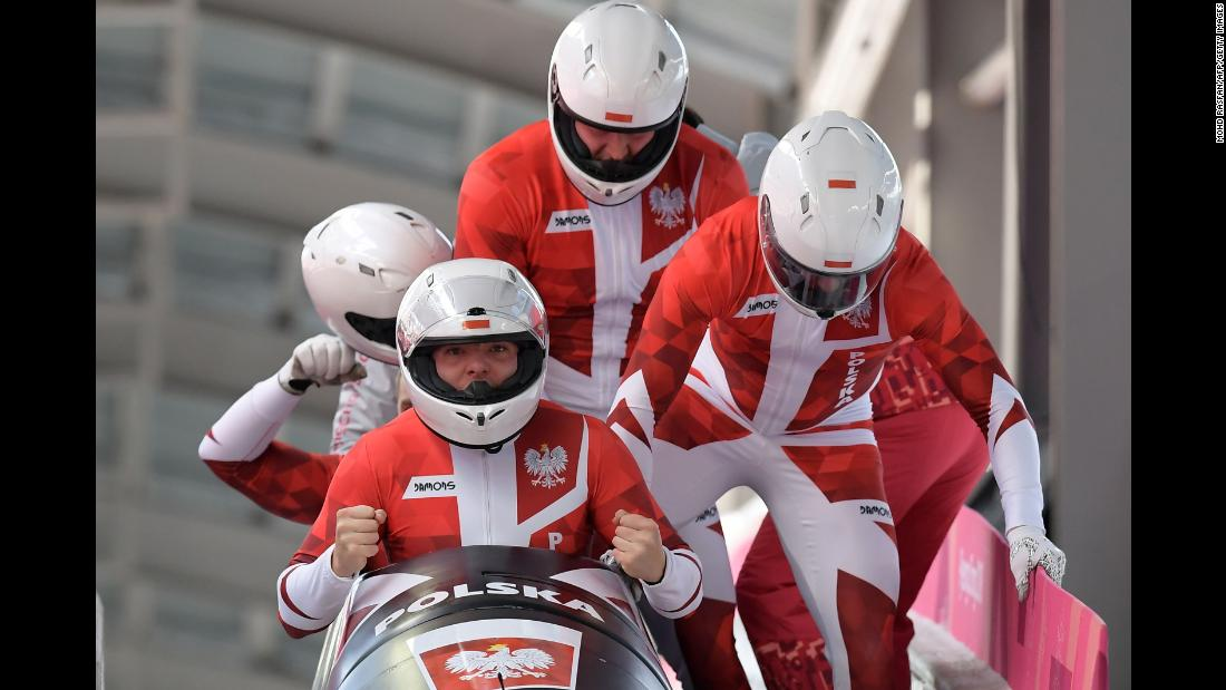 A Polish bobsled team piloted by Mateusz Luty reacts after its final run.