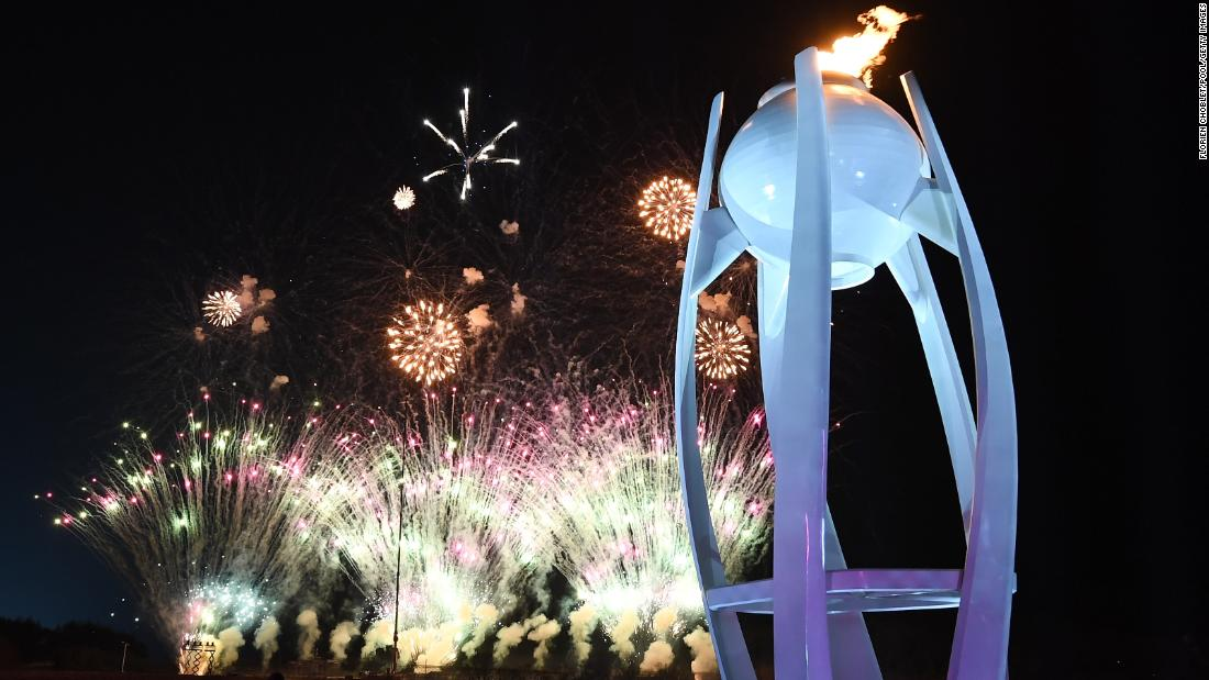 Fireworks explode behind the Olympic flame at the start of the closing ceremony.