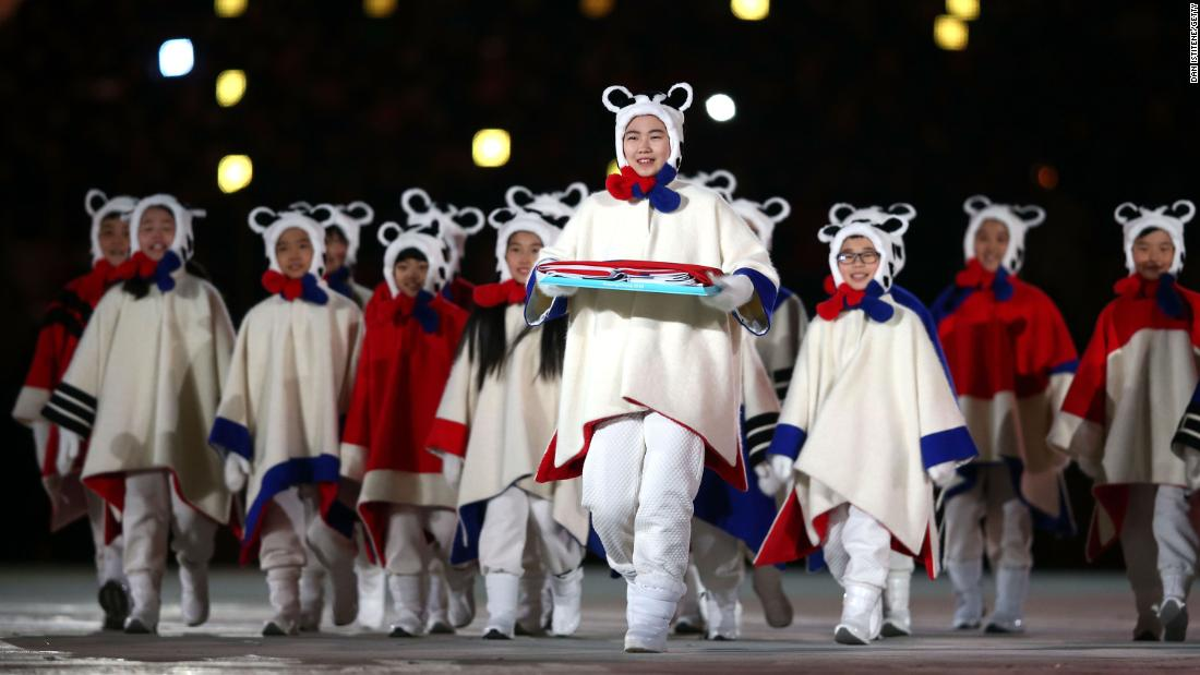 Performers carry the South Korean flag during the closing ceremony.
