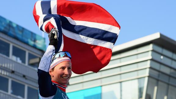 Marit Bjoergen holds aloft the Norwegian flag after winning her eighth Olympic gold medal.