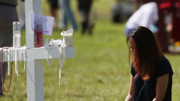 PARKLAND, FL - FEBRUARY 17: A young girl sits at a temporary memorial at Pine Trails Park on February 17, 2018 in Parkland, Florida. Police have arrested former student Nikolas Cruz and charged him with 17 murders for the shooting at Marjory Stoneman Douglas High School on February 14.  (Photo by Mark Wilson/Getty Images)