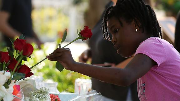 PARKLAND, FL - FEBRUARY 17: People bring flowers to a temporary memorial at Pine Trails Park on February 17, 2018 in Parkland, Florida. Police have arrested former student Nikolas Cruz and charged him with 17 murders for the shooting at Marjory Stoneman Douglas High School on February 14.  (Photo by Mark Wilson/Getty Images)