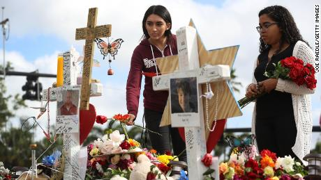PARKLAND, FL - FEBRUARY 20:  Marissa Rodriguez (L) and Ambar Ramirez visit a makeshift memorial setup in front of Marjory Stoneman Douglas High School in memory of the 17 people that were killed on February 14, on February 20, 2018 in Parkland, Florida. Police arrested 19-year-old former student Nikolas Cruz for killing 17 people at the high school.  (Photo by Joe Raedle/Getty Images)