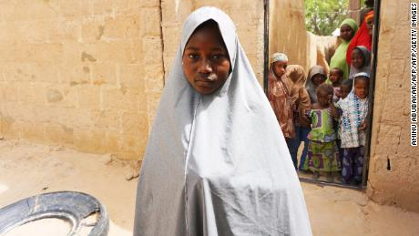 Hassana Mohammed, 13, who scaled a fence to escape an attack by armed men at her Government Girls Science and Technical College, stands outside her home in Dapchi, Nigeria, )
