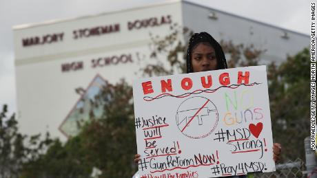 PARKLAND, FL - FEBRUARY 20:  Tyra Heman, a senior at Marjory Stoneman Douglas High School, holds a sign that reads, 'Enough No Guns,' in front of the school where 17 people that were killed on February 14, on February 19, 2018 in Parkland, Florida. Police arrested 19-year-old former student Nikolas Cruz for killing 17 people at the high school.  (Photo by Joe Raedle/Getty Images)