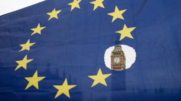 """A pro-remain protester holds up an EU flag with one of the stars symbolically cut out in front of the Houses of Parliament shortly after British Prime Minister Theresa May announced to the House of Commons that Article 50 had been triggered in London on March 29, 2017.  Prime Minister Theresa May today said there could be """"no turning back"""" and called for national unity, after notifying the EU of Britain"""