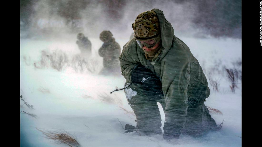 Air Force Staff Sgt. Benjamin Reynolds crouches in helicopter rotor wash during a training exercise in North Dakota's Turtle Mountain State Forest on Wednesday, February 14. The exercise simulated medical evacuations.