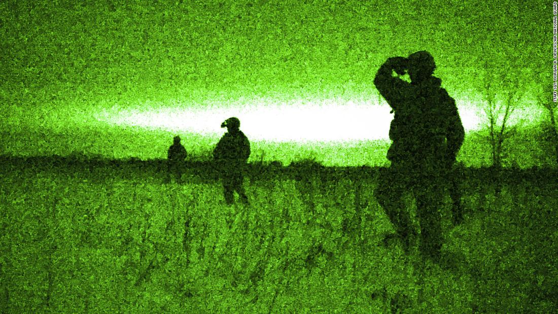 US airmen, seen through a night-vision device, hike in a tactical formation during an exercise in Kansasville, Wisconsin, on Saturday, February 10.