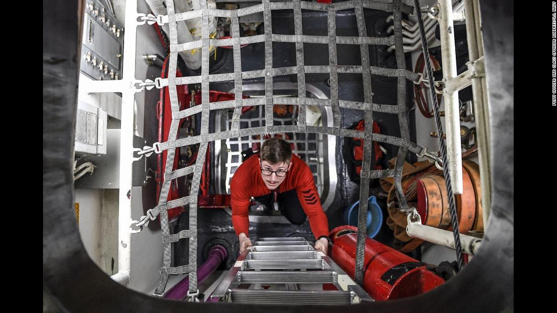 Navy Petty Officer 1st Class Nicholas Beemer climbs a ladder aboard the USS Theodore Roosevelt on Saturday, February 3.