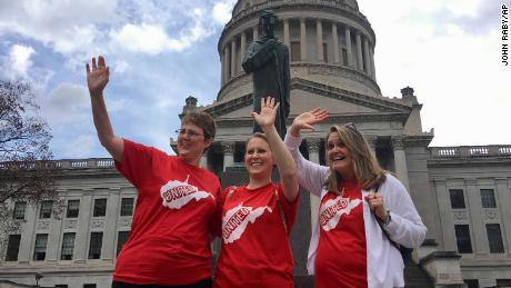 Striking teachers Michelle Myers, left, Holly O'Neil, center, and Suzanne Varner of McNinch Primary School in Moundville, W.Va. wave to passing cars outside the state Capitol in Charleston, W.Va,  Friday, Feb. 23, 2018. West Virginia teachers are continuing their walkout for a second day as thousands showed up again at the state Capitol to press the Legislature to help them with pay and benefits. (AP Photo/John Raby)