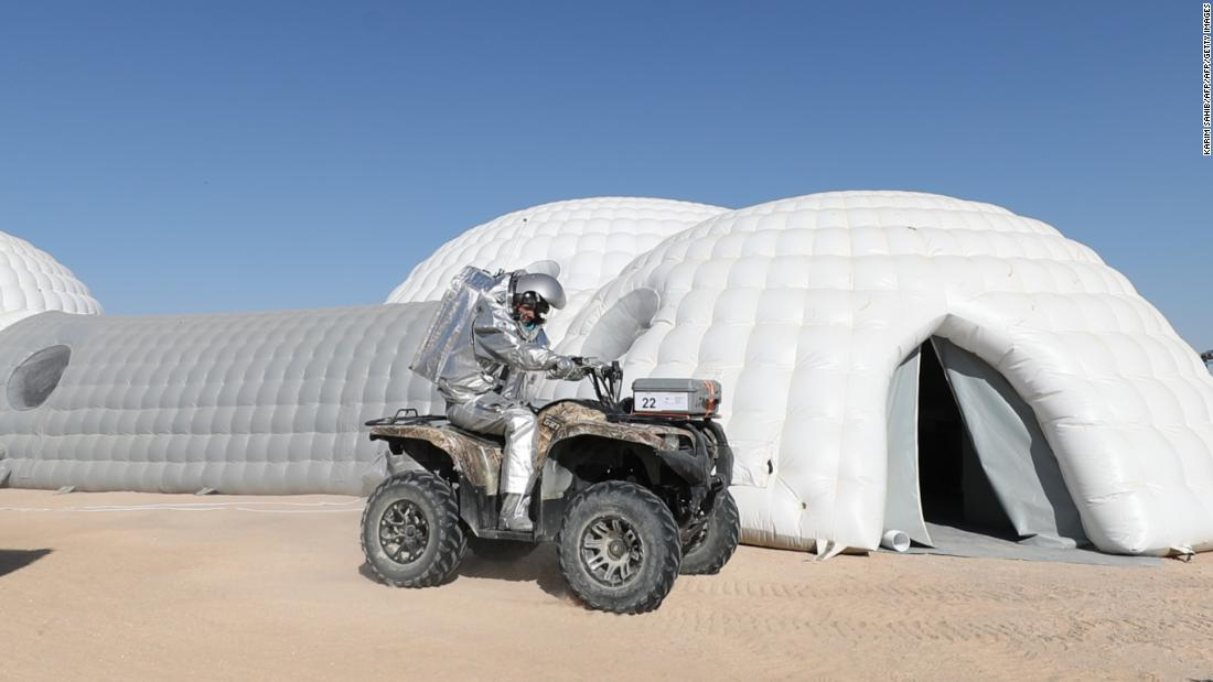 An analog astronaut on a buggy stops outside inflatable residences for members of the AMADEE-18 mission in Oman's Dhofar region.