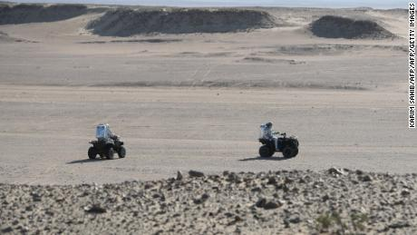 Members of the AMADEE-18 Mars simulation mission ride all-terrain vehicles while wearing spacesuits in Oman's Dhofar desert.