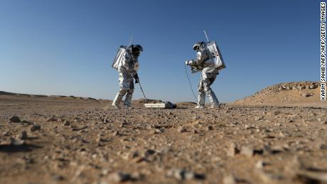 Members of the AMADEE-18 Mars simulation mission wear spacesuits while conducting scientific experiments in Oman's Dhofar desert.