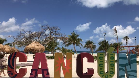 Tourist walks along the beach in Cancun, Quintana Roo, Mexico on March 28, 2017. Cancun (in Maya, kaan and kun, meaning 'cradle or nest of snakes') is the most recognized Mexican tourist center in the world and one of the most visited by foreigns. The Puerto Morelos Reef has been declared a National Park and forms part of the second largest barrier reef in the world. / AFP PHOTO / DANIEL SLIM (Photo credit should read DANIEL SLIM/AFP/Getty Images)