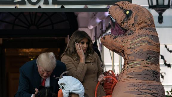 The Trumps hand out candy to children during a White House Halloween event.