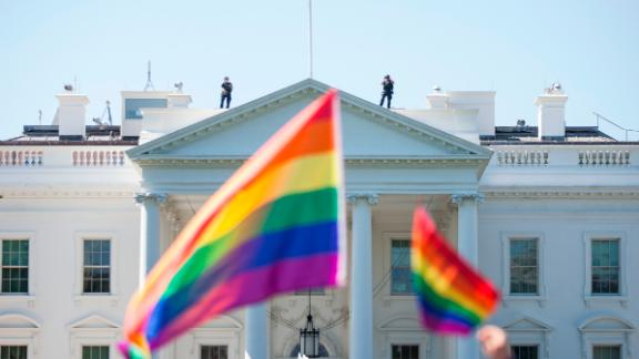 Demonstrators in Washington carry rainbow flags past the White House during the Equality March for Unity and Peace on June 11, 2017.