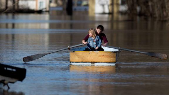 Emily Snyder and her daughter, Skyler, check out their home in their flooded neighborhood in Plainfield Township, Michigan, on Monday.
